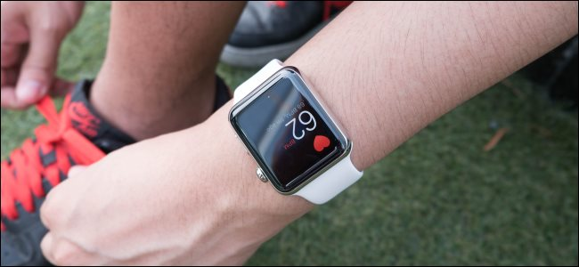 Un corredor que ata sus zapatillas mientras lleva puesto un Apple Watch.